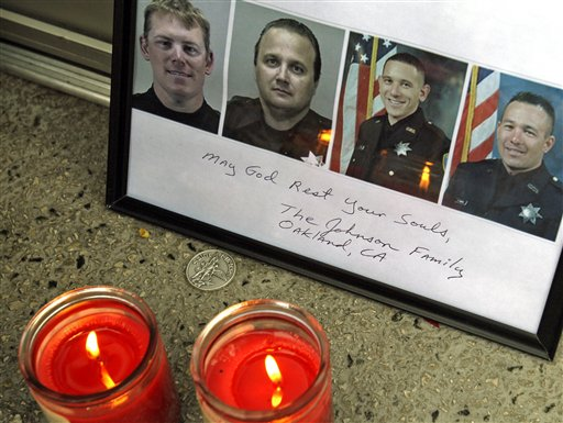 A memorial to four officers killed in the line of duty by a man wanted on a parole violation is seen Tuesday, March 24, 2009, at police headquarters in Oakland, Calif. Oakland's police department has been left stunned after one officer died after being taken off life support and three others were killed during confrontations with the parolee on Saturday, the department's worst single-day death toll. (AP Photo/Ben Margot)