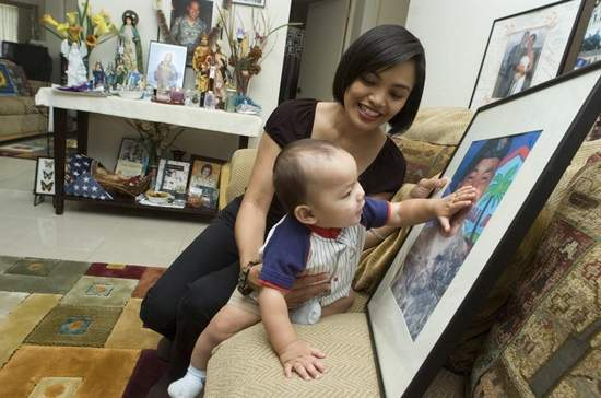 Pictures of dad: Emely Leon Guerrero holds Jude Steven Leon Guerrero, as he reaches for a picture of his father, Guam Army National Guard Sgt. Brian Leon Guerrero, at their home in Tamuning on May 22. Jude Steven Leon Guerrero was born shortly after Sgt. Leon Guerrero was killed while being deployed to Afghanistan in July 2008. (Masako Watanabe/Pacific Daily News/mwatanabe@guamp)